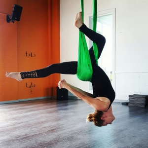 Aerial yoga instructor hanging in green silk hammock